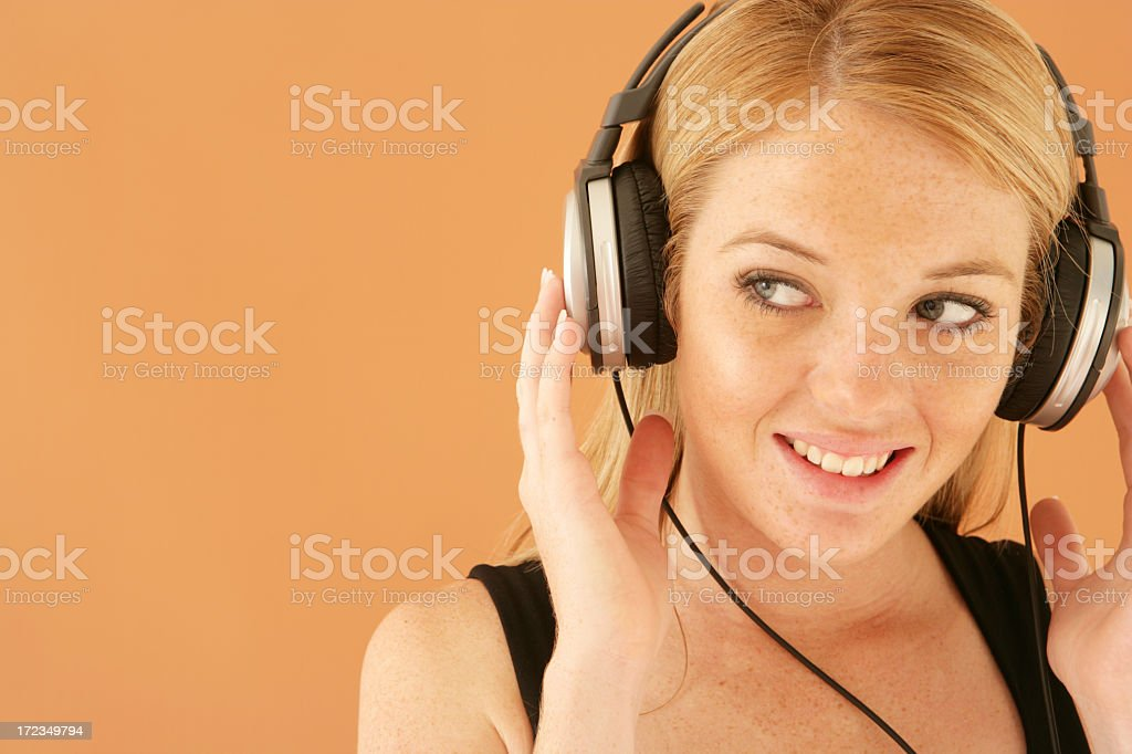 Smiling woman with earphones on against an orange background royalty-free stock photo