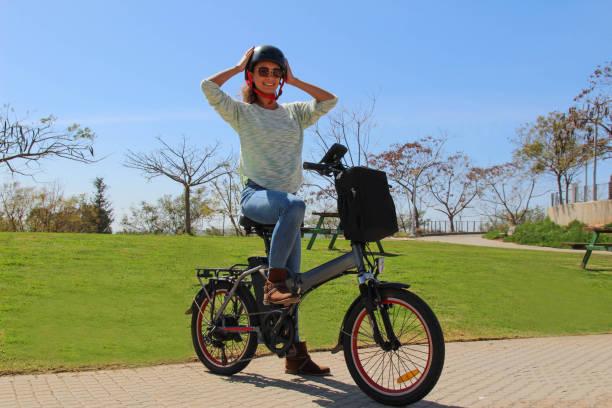 eine lächelnde frau mit elektro-fahrrad im park das tragen eines helmes - elektrorad stock-fotos und bilder