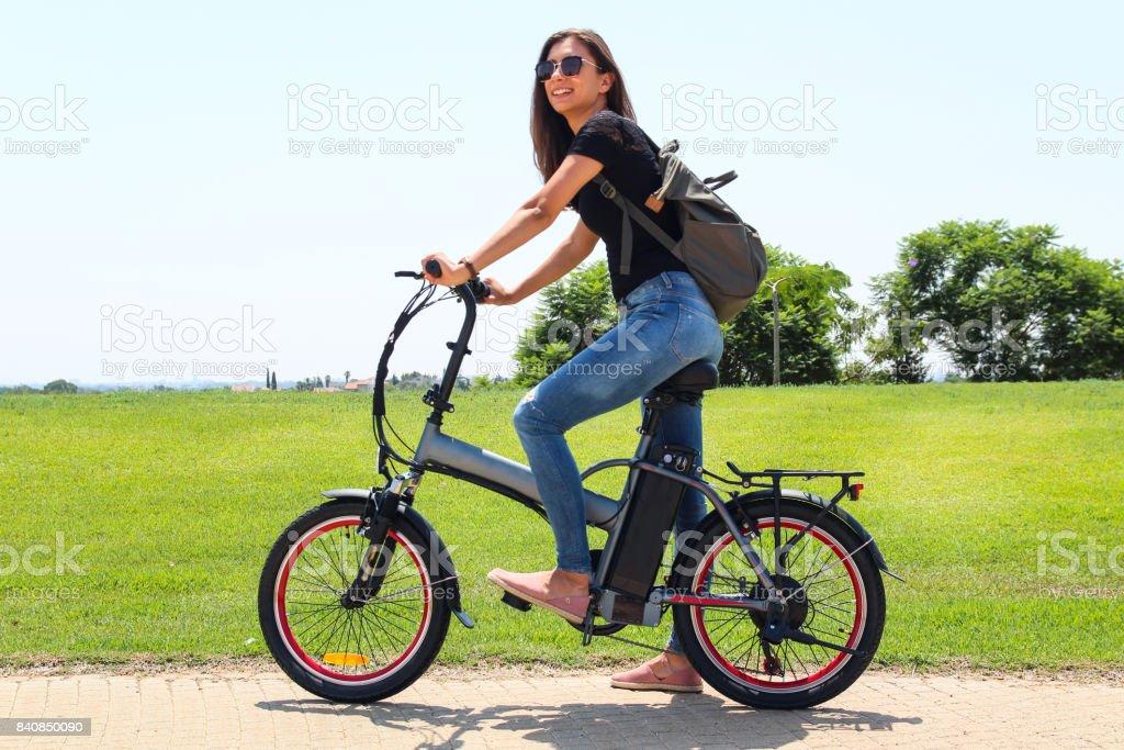 Una mujer sonriente con moto eléctrica e en el Parque - foto de stock