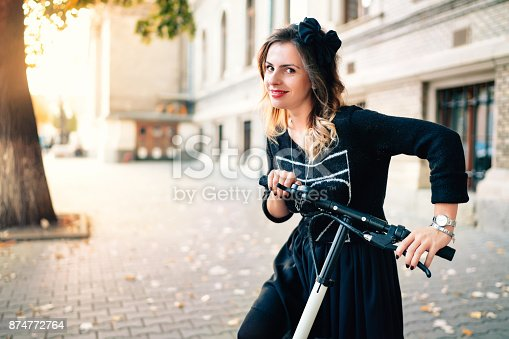 874772840istockphoto Smiling woman with electric kick scooter on a beautiful autumn day enjoying sunset. Portrait of girl using technology as means of transportation 874772764