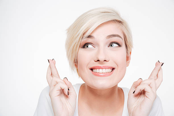Smiling woman with fingers crossed gesture stock photo