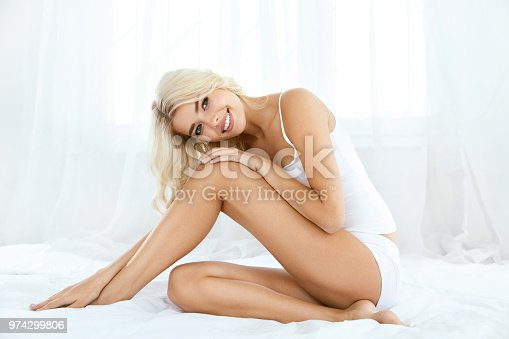 istock Smiling Woman With Fit Body And Beautiful Legs On White Bed 974299806