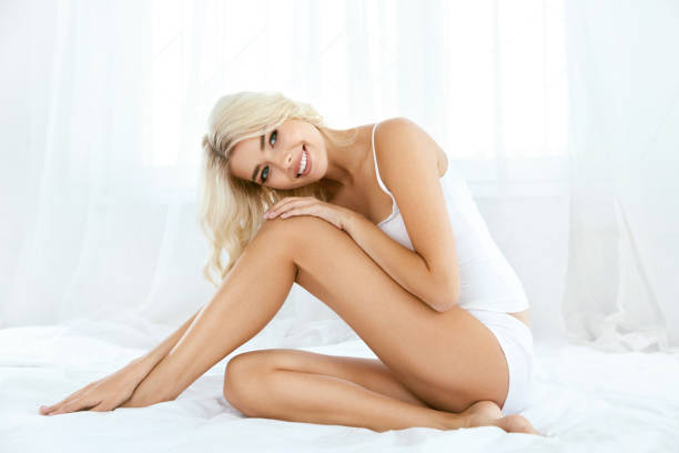 Smiling Woman With Fit Body And Beautiful Legs On White Bed stock photo
