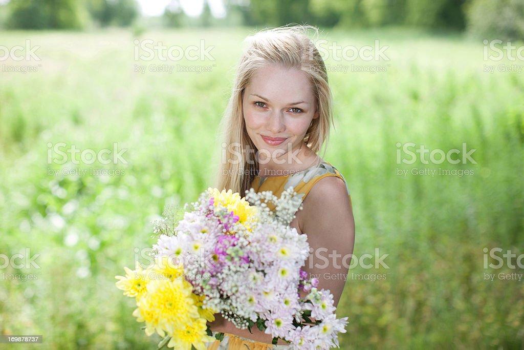 Femme souriante avec des fleurs dans la campagne du terrain - Photo