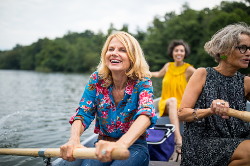 Smiling woman with friend rowing boat in lake