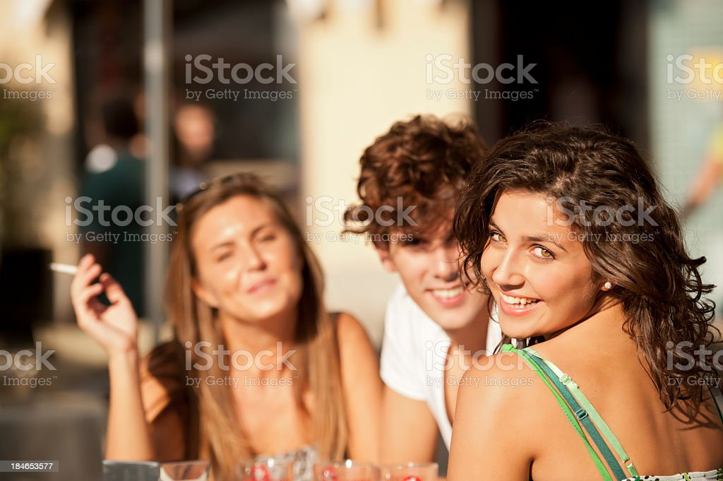 Smiling woman with friends is sitting in a cafe royalty-free stock photo