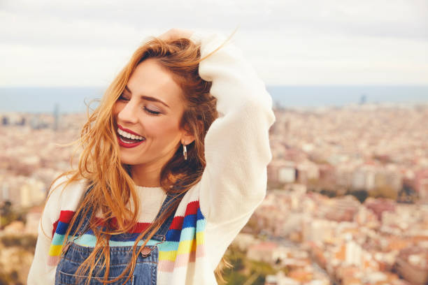 Smiling woman with hand in hair against cityscape stock photo