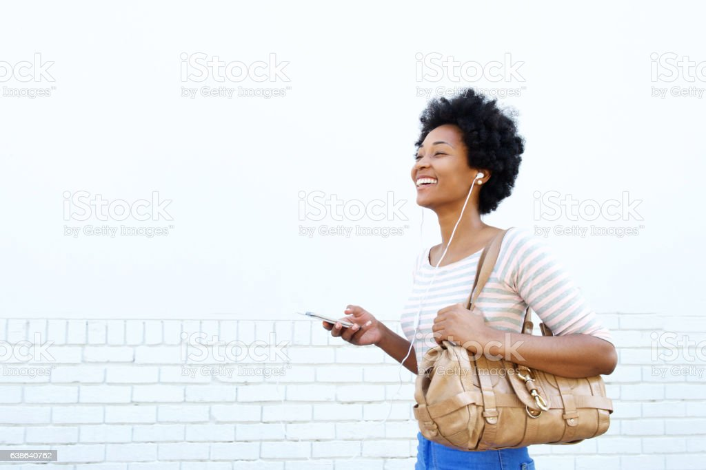 smiling woman with handbag listening to music - foto de stock