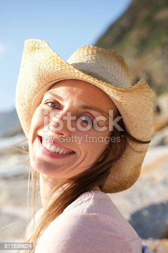 istock Smiling woman with hat at the beach 511539624