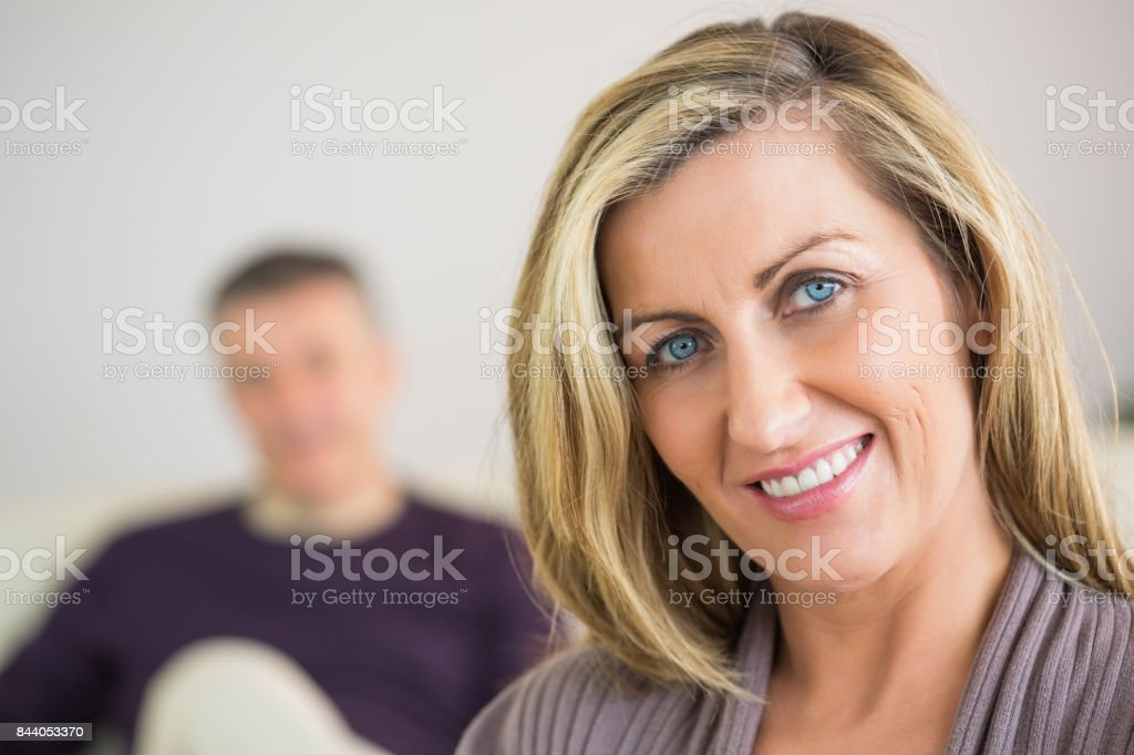Smiling woman with her husband in the background stock photo