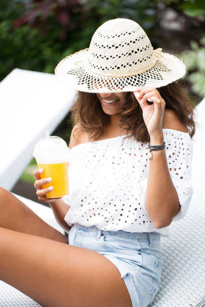 Smiling Woman With Lemonade on Chaise Longue stock photo