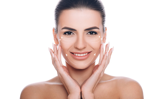 istock smiling woman with lifting arrows on face. Concept of skin lifting 1139925115