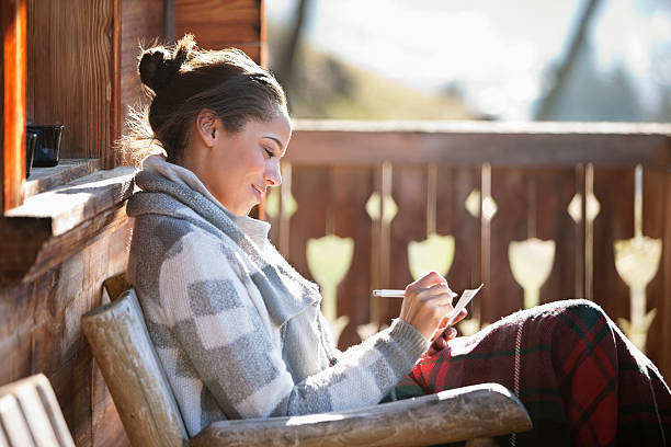 Smiling woman with paper and pen on cabin porch stock photo