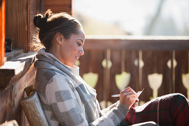 lächelnde frau mit papier und stift auf kabine veranda - veranda decke stock-fotos und bilder