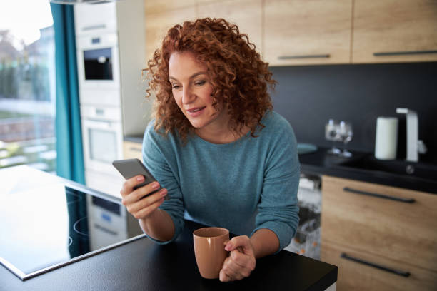 Smiling woman with phone in kitchen stock photo stock photo