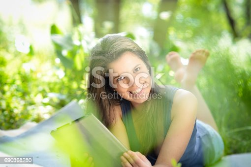 A smiling young woman reading from a tablet computer in a forest.