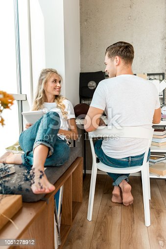 istock smiling woman with tablet sitting near boyfriend at home 1051278912