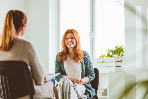 Mature woman smiling while discussing with therapist. Psychotherapist is with female at community center. They are sitting on chairs.