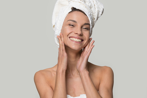 istock Smiling woman with towel on head touch clean healthy skin 1147400532