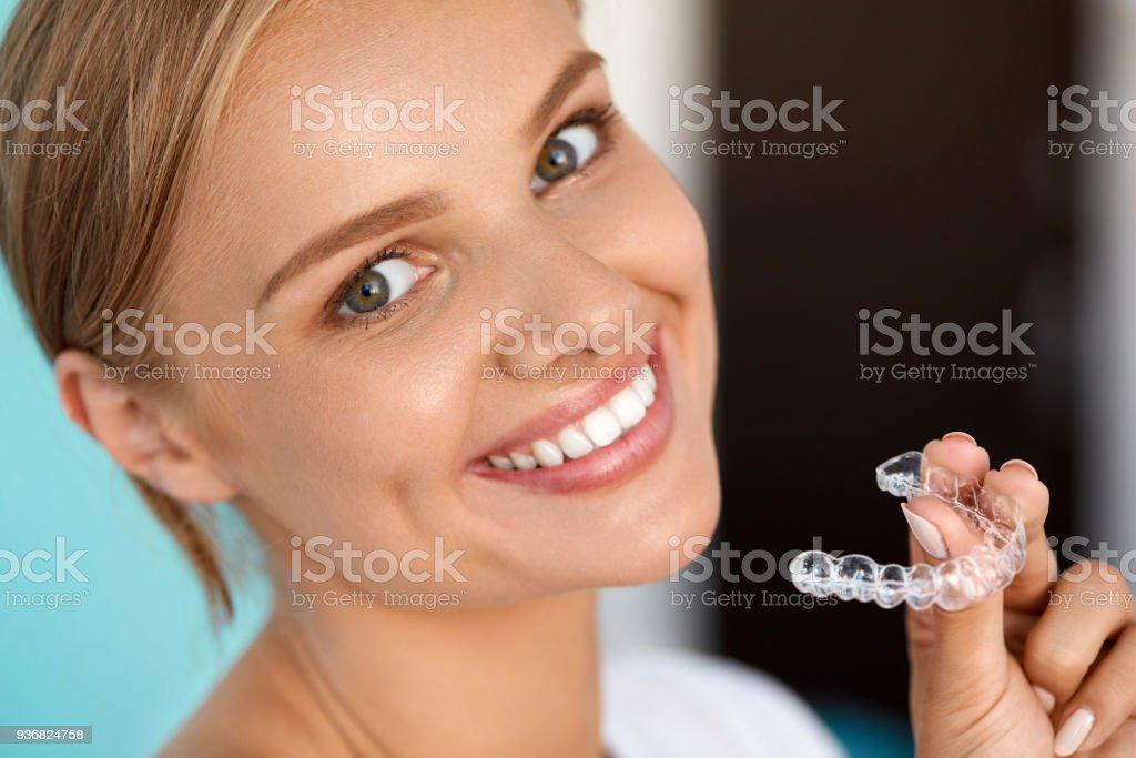 2e0431ef8 Mulher sorridente com dentes brancos segurando a bandeja de clareamento dos  dentes foto royalty-free