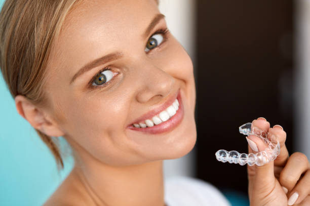 Smiling Woman With White Teeth Holding Teeth Whitening Tray White Teeth. Closeup Portrait Of Beautiful Happy Woman With Perfect White Smile Using Teeth Whitening Tray. Smiling Girl Holding Medical Invisible Braces. Dental Health Concept. High Resolution Image straight stock pictures, royalty-free photos & images