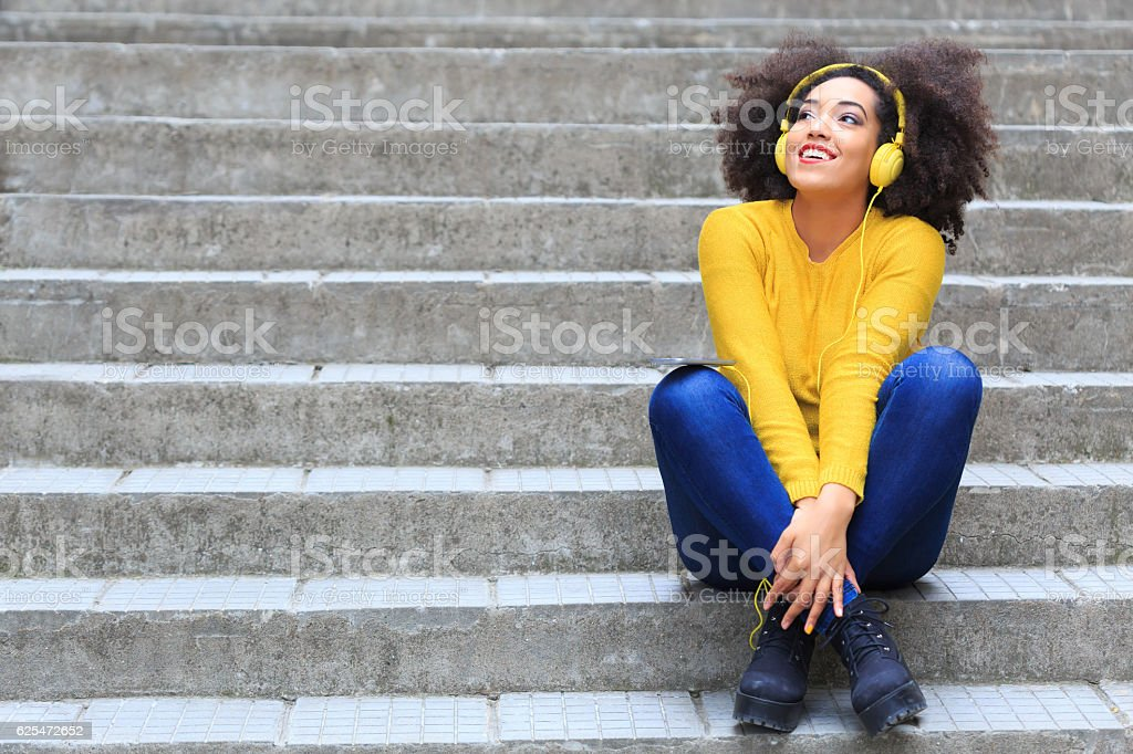 Smiling woman with yellow headphones sitting on stairs - foto de acervo