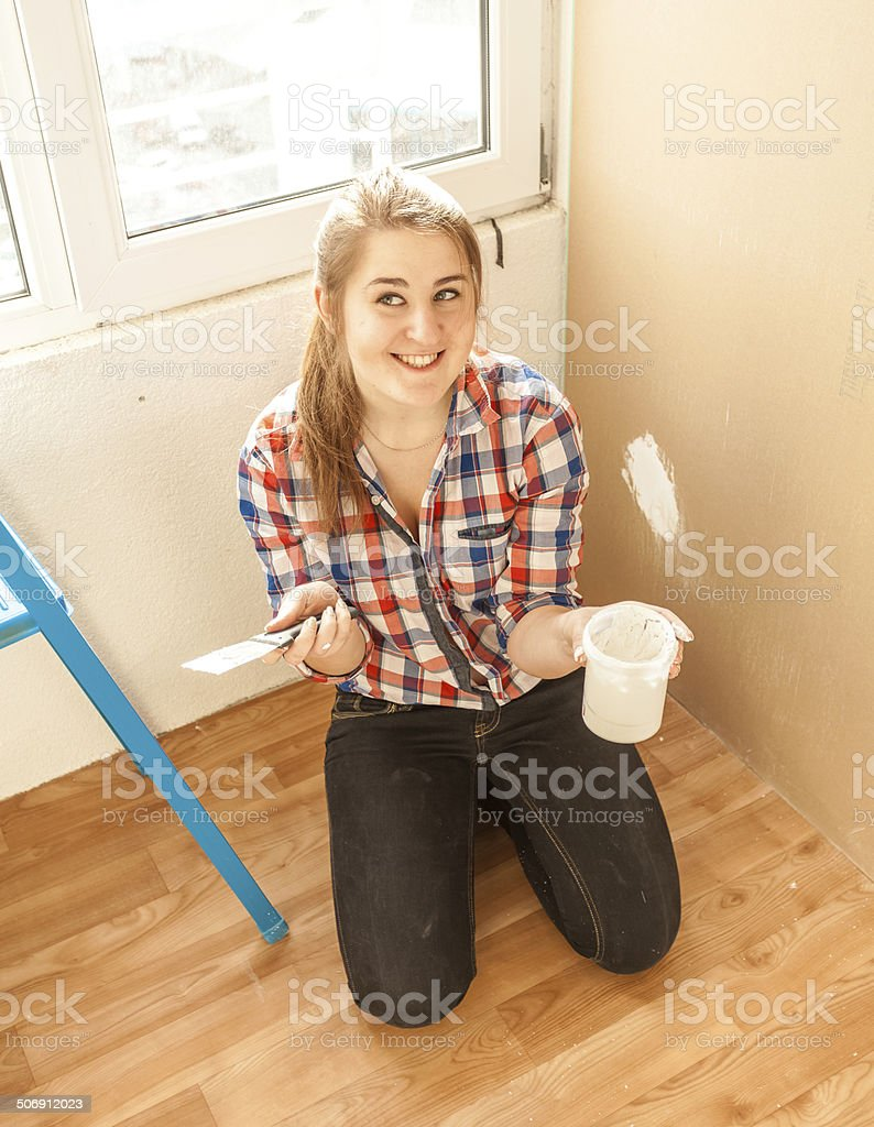 Smiling woman worker holding spatula and putty stock photo