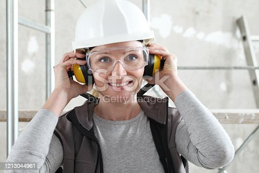 smiling woman worker portrait wearing helmet, safety glasses and hearing protection headphones, scaffolding interior construction site background