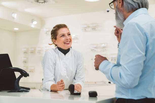 Smiling woman working in the optics shop leaning on the counter, talking to a senior man stock photo