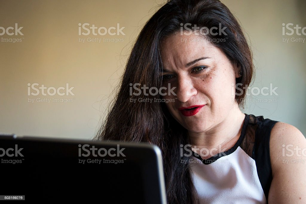 Smiling woman working on her laptop at home office desktop stock photo