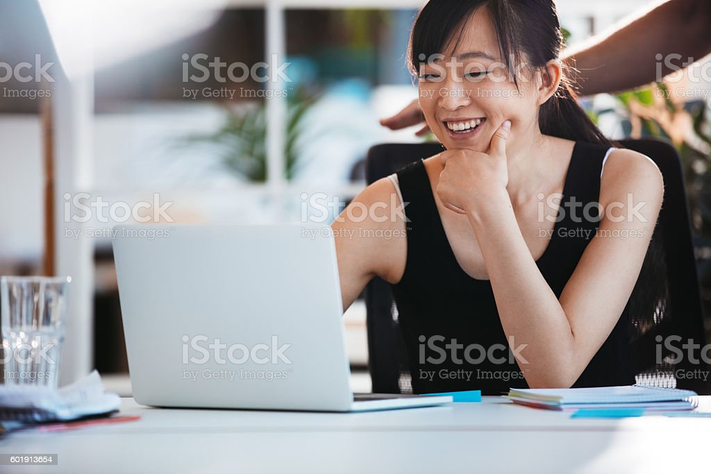 Smiling woman working on laptop at office stock photo