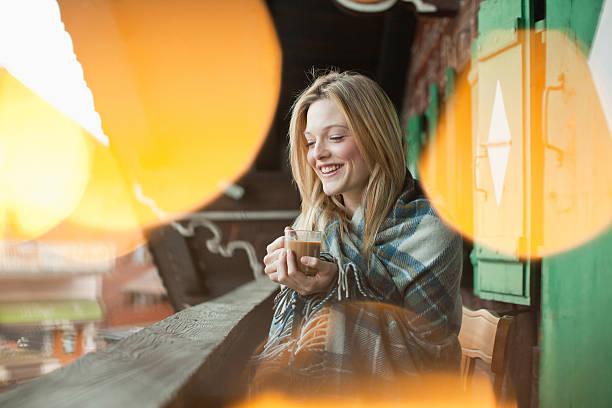 lächelnde frau in eine decke gewickelt und trinken kaffee - veranda decke stock-fotos und bilder