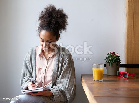 istock Smiling woman writing on note pad at home 525585737