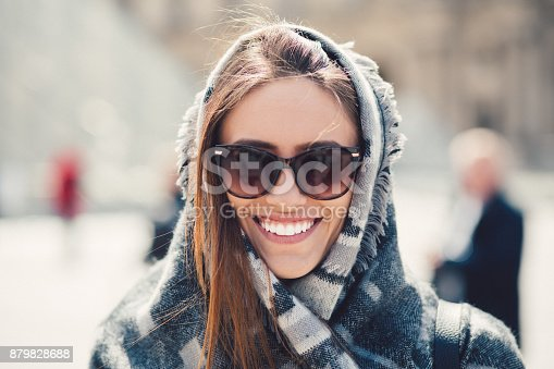 Young woman wrapped in scarf smiling to the camera