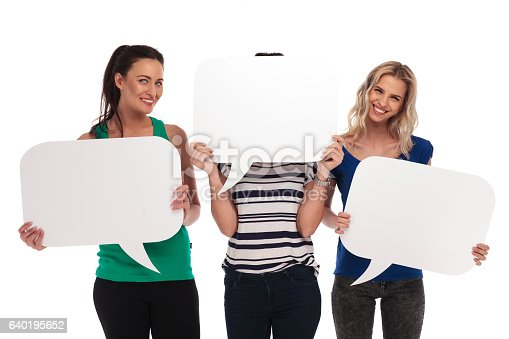 istock Smiling women holding  speech bubbles, one  covering her face 640195652