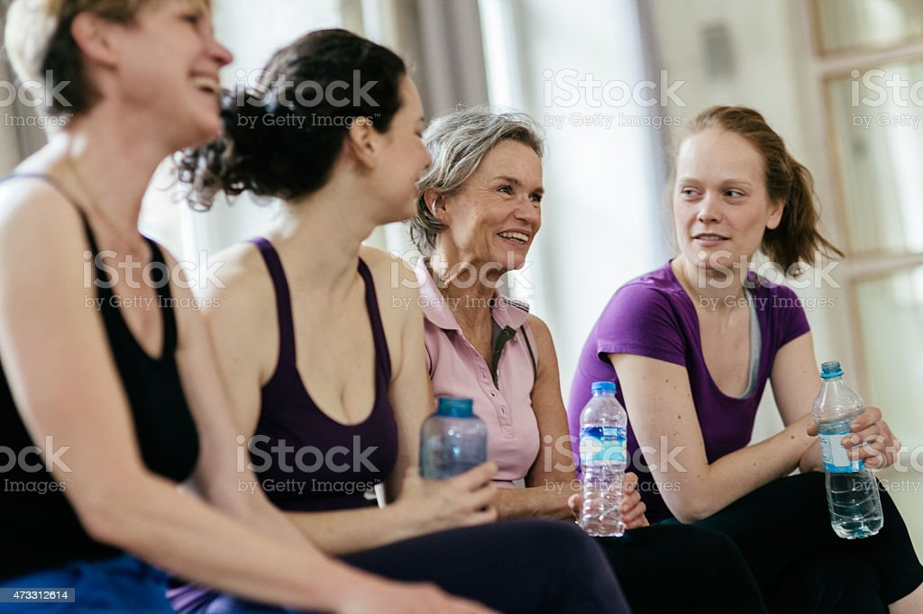 Smiling women holding water bottles while relaxing in gym stock photo