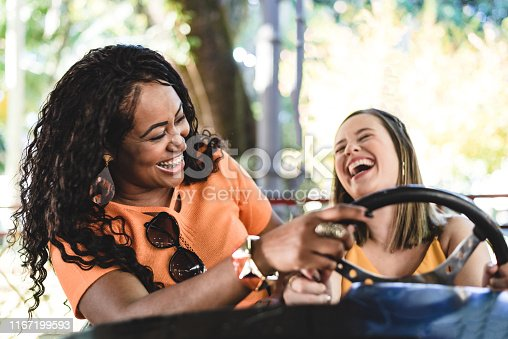 1035136022 istock photo Smiling women in the amusement park cart 1167199593