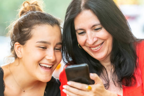 Smiling women looking at a smart phone stock photo