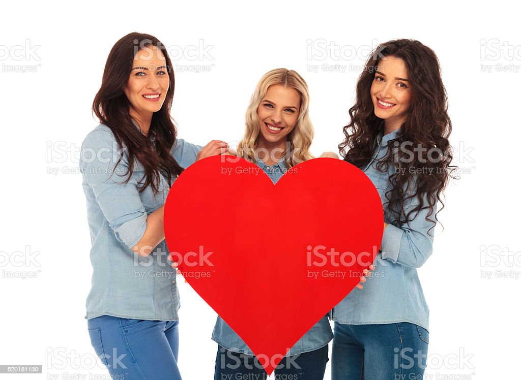 3 smiling women offering their big red heart to you stock photo