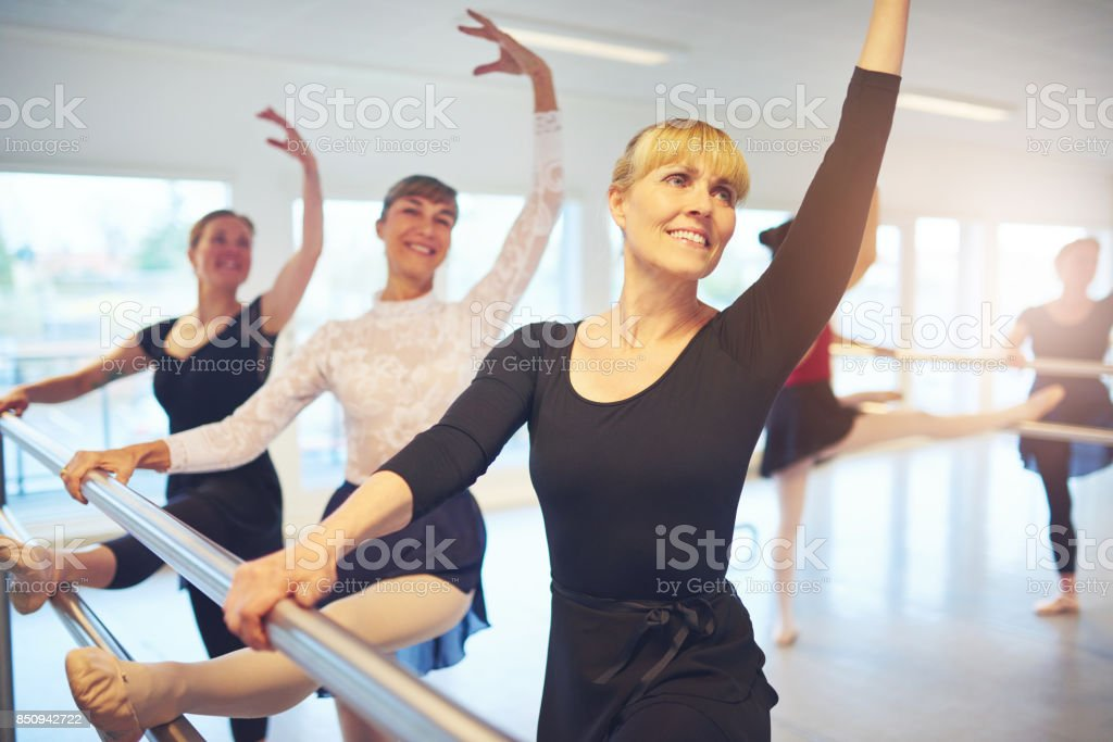 Smiling Women Posing And Doing Gymnastics In Ballet Class