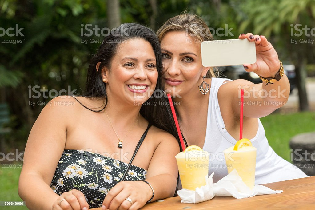 Smiling women posing together taking a selfie royalty-free stock photo