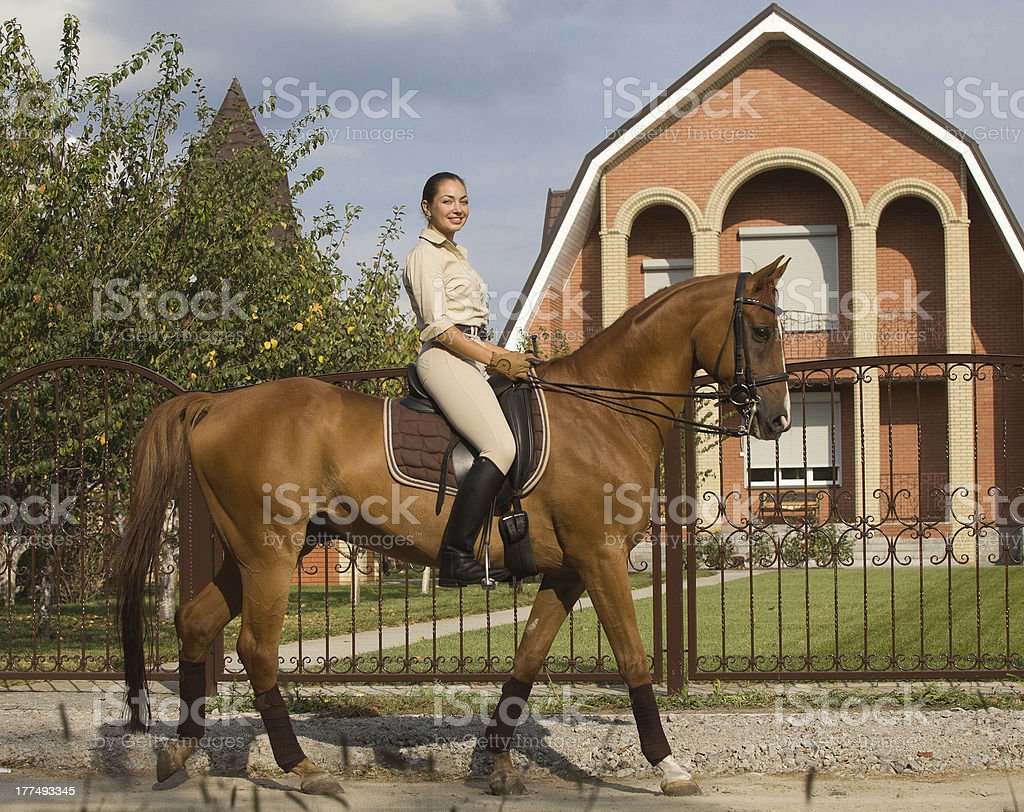 Smiling women riding a brown horse in countryside. royalty-free stock photo