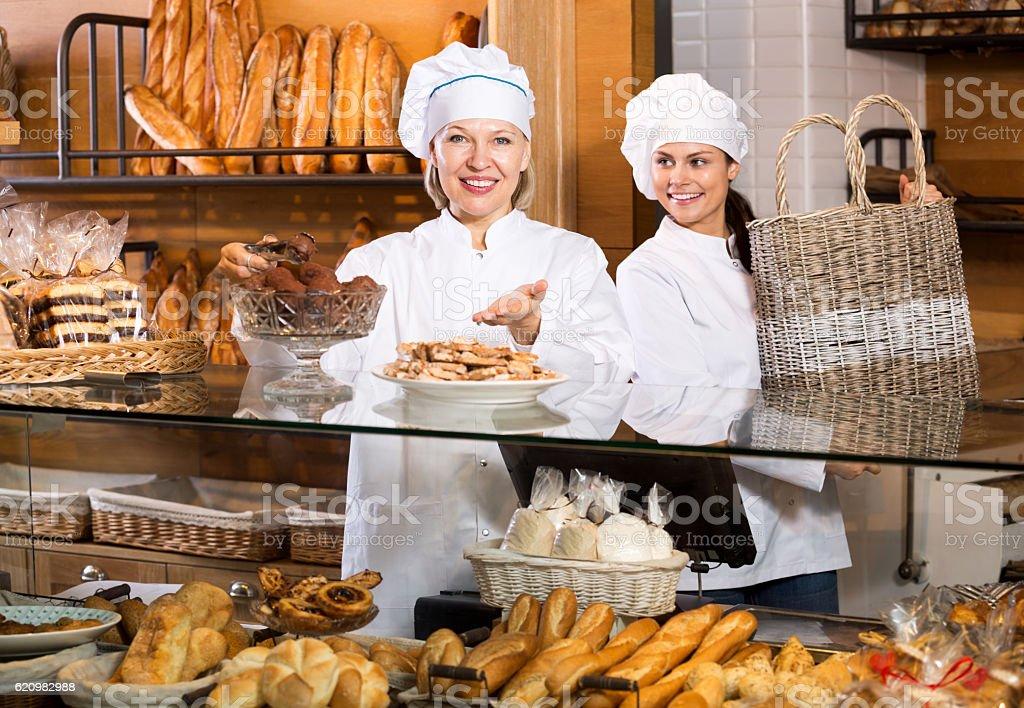 Mulheres sorridentes de venda de doces e pães frescos foto royalty-free