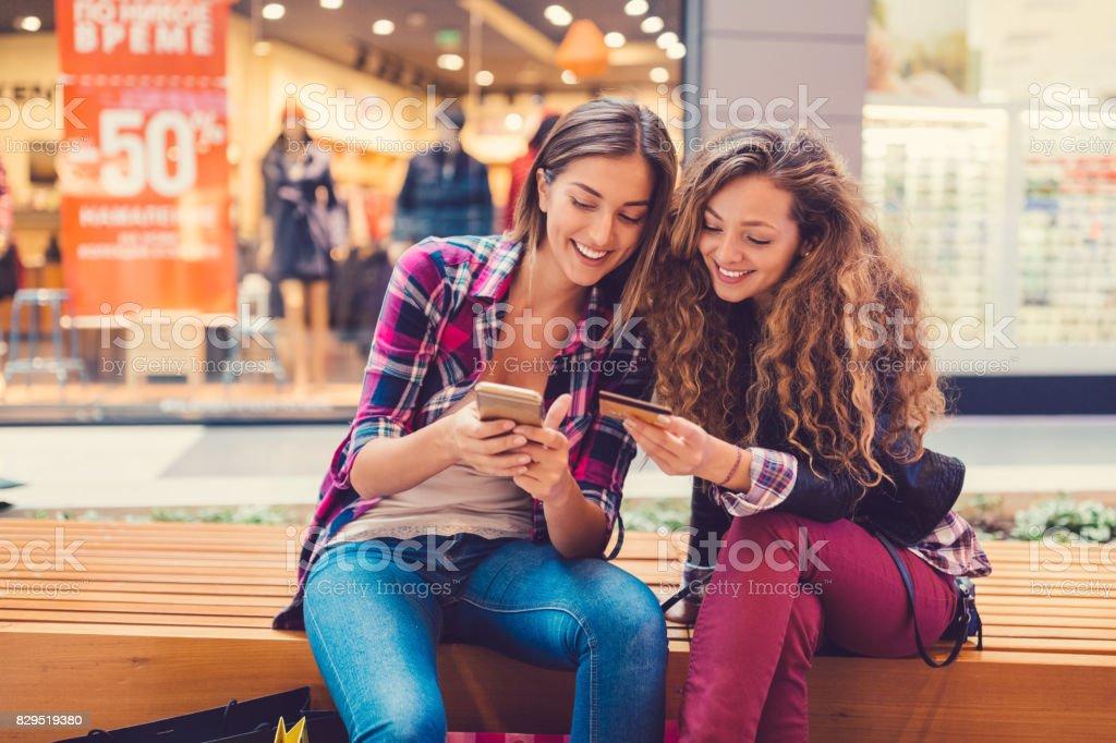 Mulheres sorridentes, compras on-line com cartão de crédito - foto de acervo
