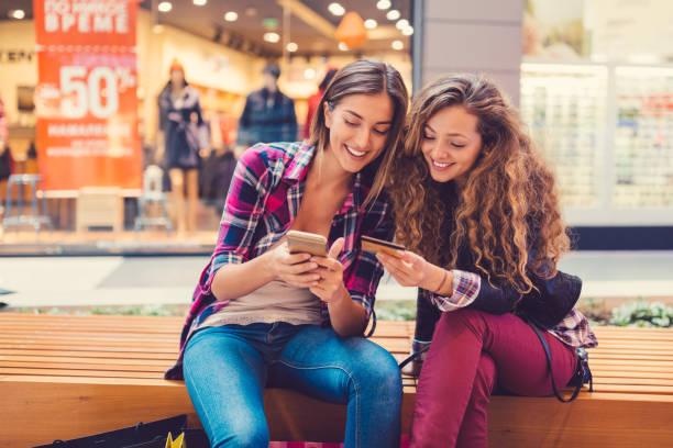 smiling women shopping online with credit card - online shopping imagens e fotografias de stock