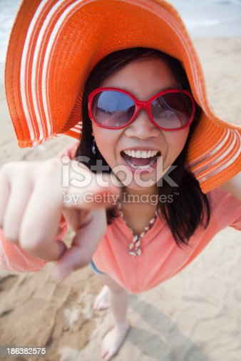 453383283 istock photo Smiling women standing on the beach pointing at camera, portrait 186382575