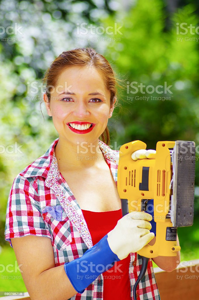 smiling women with colorfull clothes holding a eletric sander royaltyfri bildbanksbilder