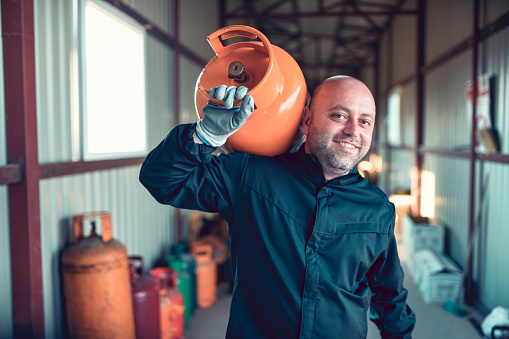Smiling Worker Carrying Gas Cylinder For Refilling