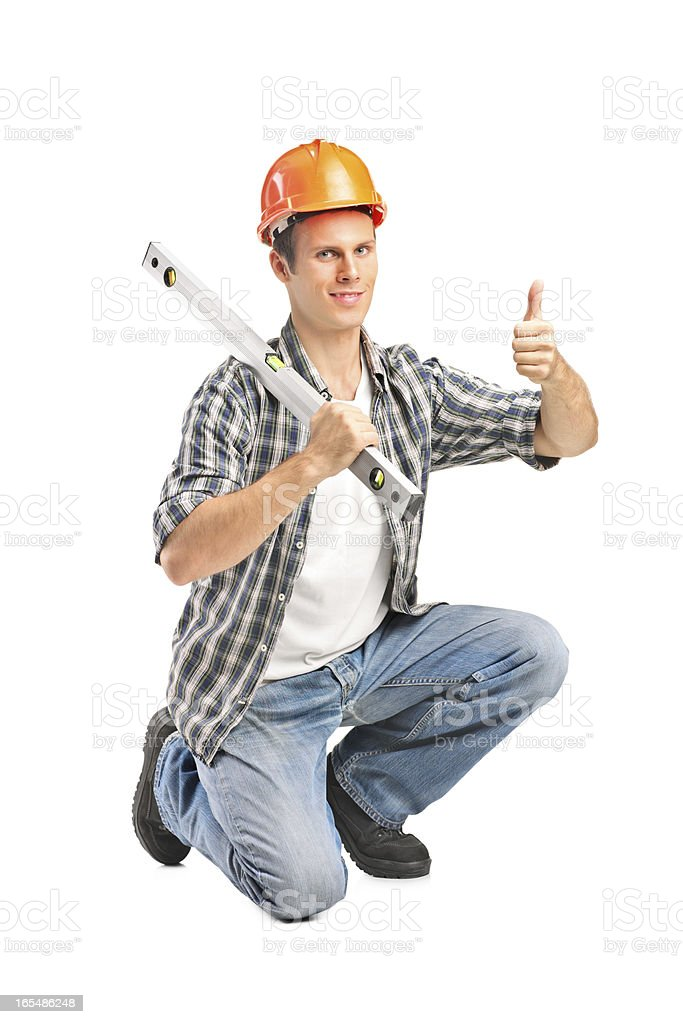 Smiling worker holding a tool and giving thumb up royalty-free stock photo