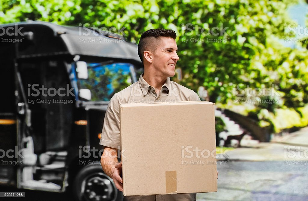 Smiling worker holding package outdoors stock photo